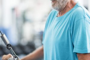 one mature man lifting a weight with a machine at the gym - active senior training hard